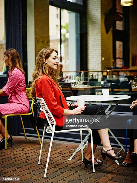 Smiling businesswoman at outdoor table of cafe