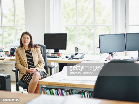 Smiling businesswoman at workstation in office