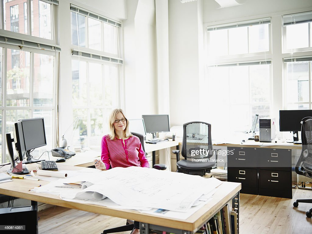 Smiling businesswoman at workstation in office : Stock Photo