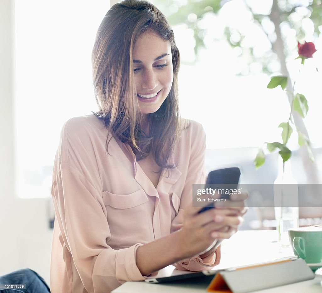 Smiling businesswoman checking cell phone : Stock Photo