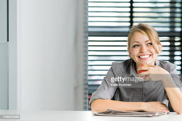 Smiling businesswoman eating apple at desk