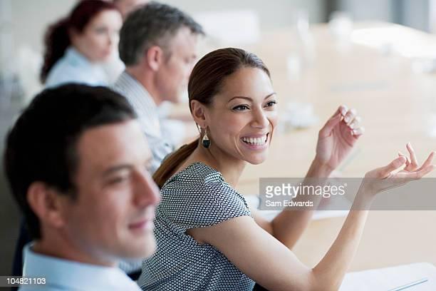 Souriant Femme d'affaires gestes de réunion en salle de conférence
