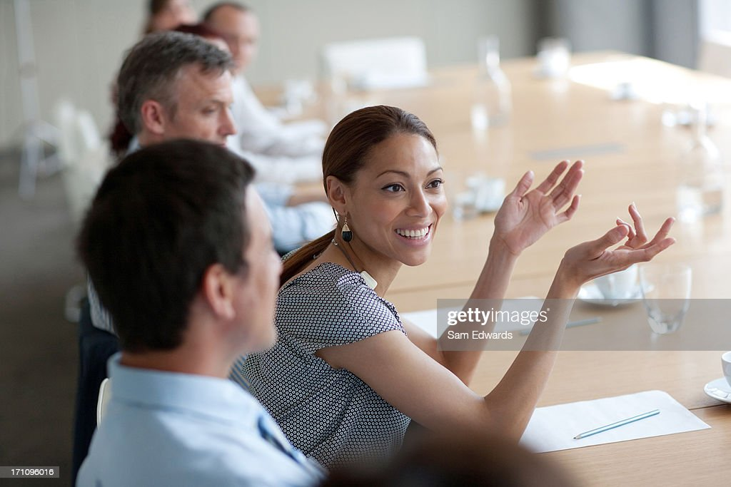 Smiling businesswoman gesturing in meeting in conference room