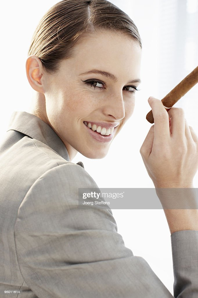 Smiling businesswoman holding cigar : Stock Photo