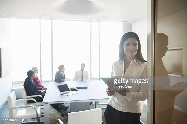 Smiling Businesswoman Holding Digital Tablet While Looking Away At Entrance