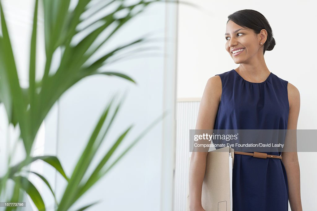 Smiling businesswoman holding folder : Stock Photo