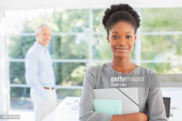 Smiling businesswoman holding paperwork in office