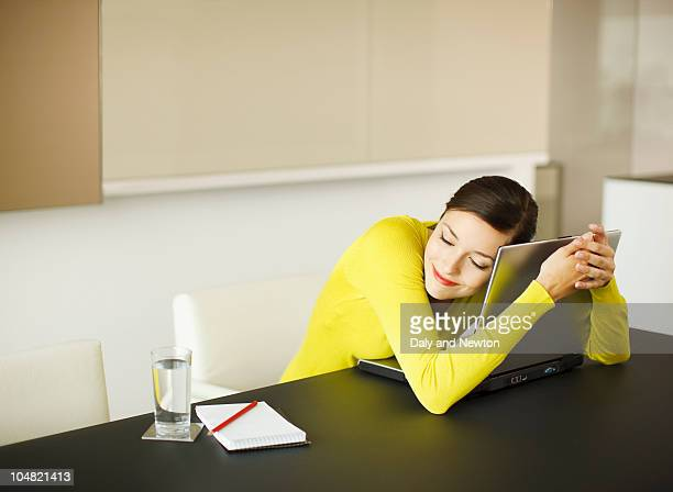 Smiling businesswoman hugging laptop in conference room