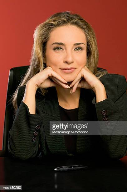 Smiling businesswoman in black suit with hands on chin against a red background, close-up