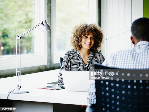 Smiling businesswoman in discussion with coworker