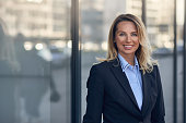 Smiling businesswoman standing in front of a large glass window on a commercial building in town with reflection and copy space