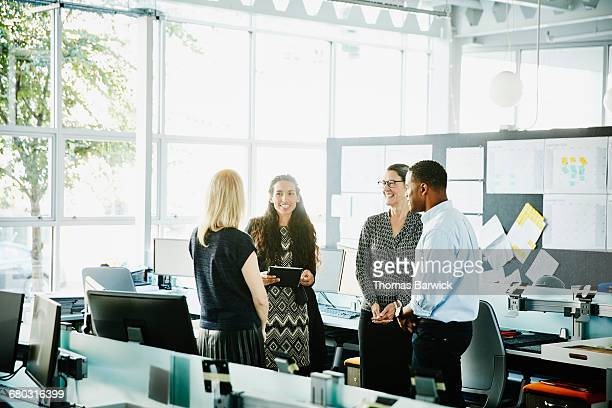 Smiling businesswoman leading informal meeting