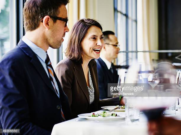 Smiling businesswoman leading lunch meeting