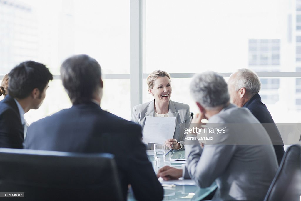 Smiling businesswoman leading meeting in conference room : Stock Photo