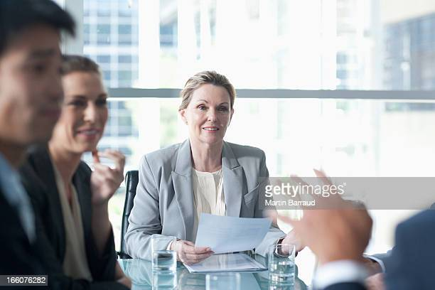 Smiling businesswoman leading meeting in conference room