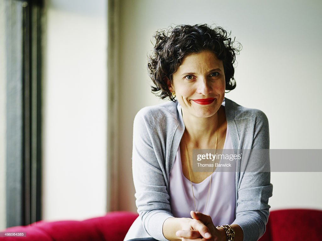 Smiling businesswoman leaning against chair