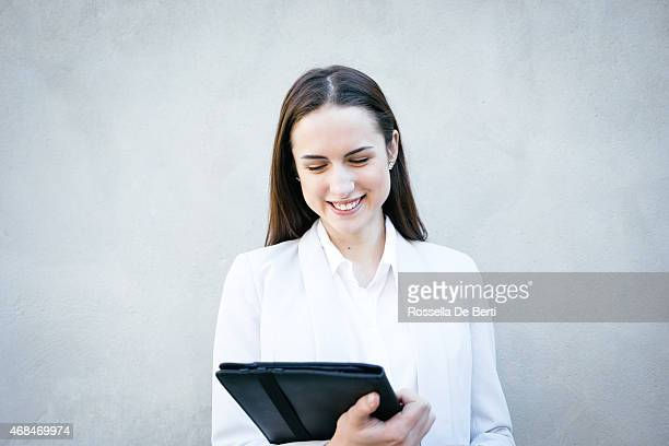 Smiling Businesswoman Leaning Against Wall Making A Video Call