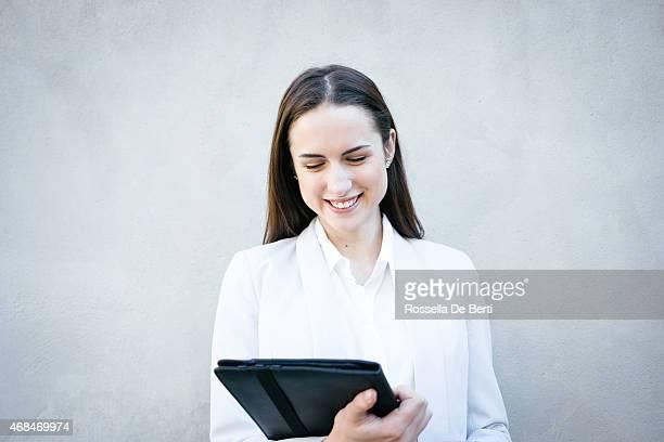 Souriant Femme d'affaires s'appuyant sur le mur de faire un appel vidéo