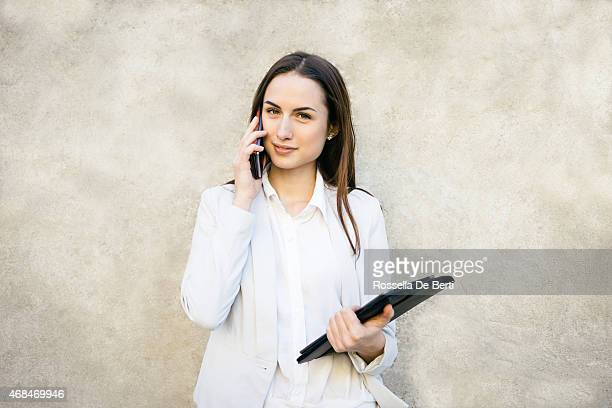 Smiling Businesswoman Leaning Against Wall Portrait