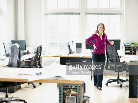 Smiling businesswoman leaning on chair in office