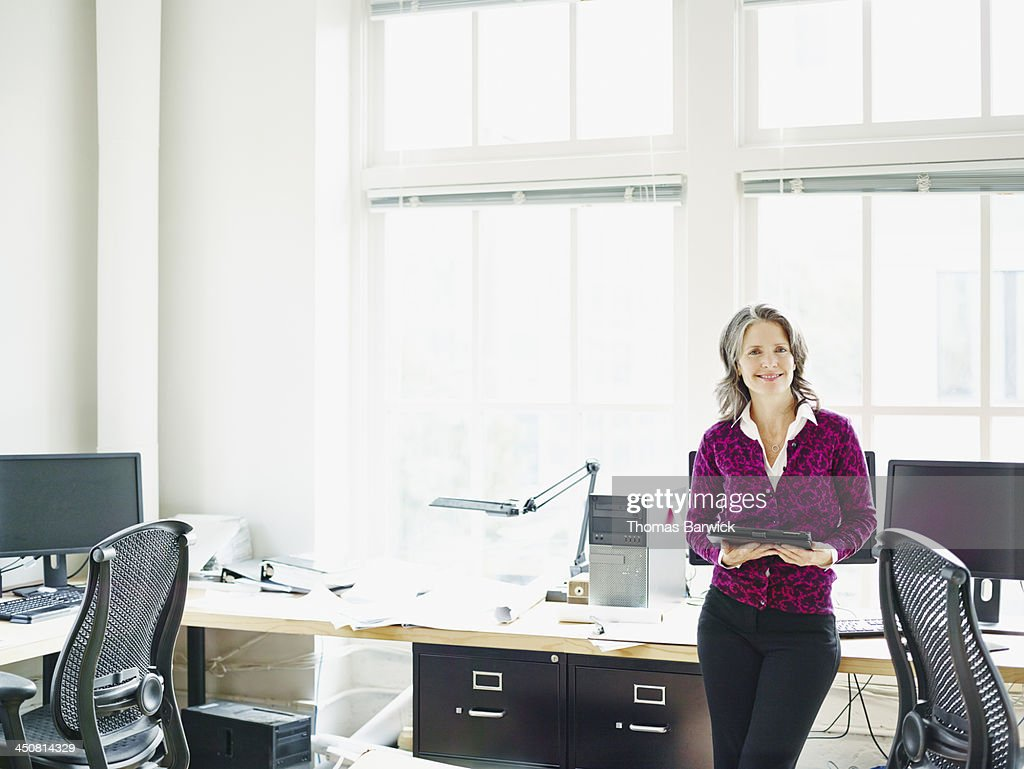 Smiling businesswoman leaning on desk in office : Stock Photo