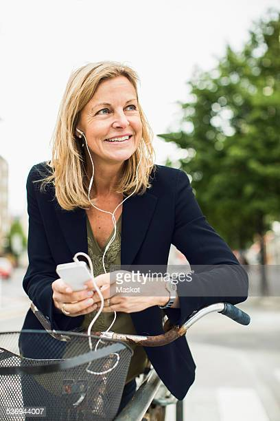 Smiling businesswoman listening music through smart phone while leaning on bicycle outdoors