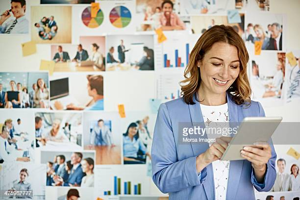 Smiling businesswoman looking at digital tablet