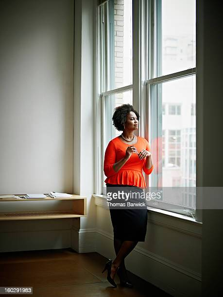 Smiling businesswoman looking out office window