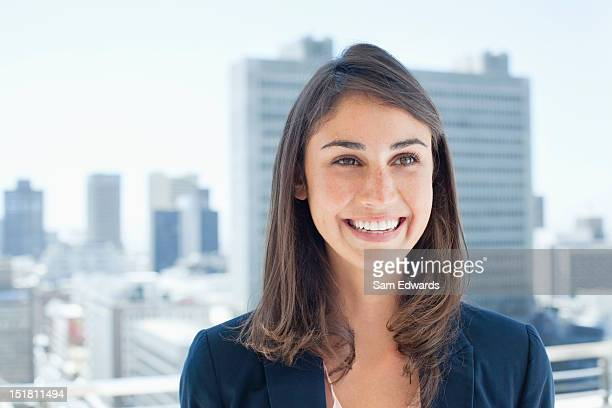 Smiling businesswoman on urban balcony