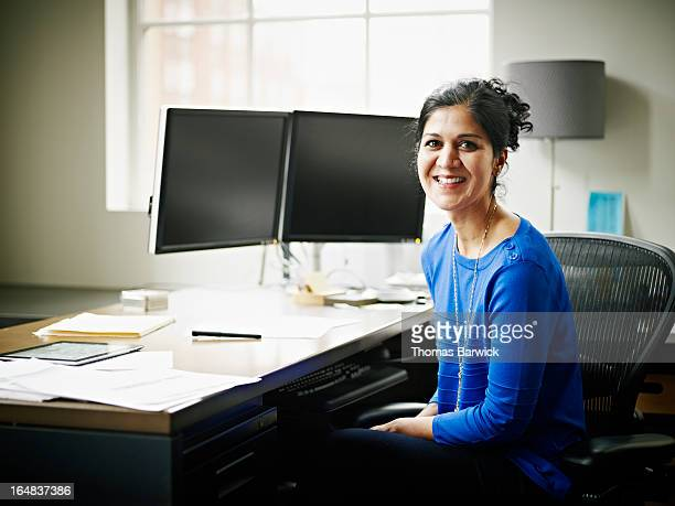 Smiling businesswoman seated at workstation