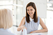 Smiling happy businesswoman shaking hand greeting female partner as concept of respect, collaboration, business deal, friendly hr handshaking new hire at job interview, making good first impression