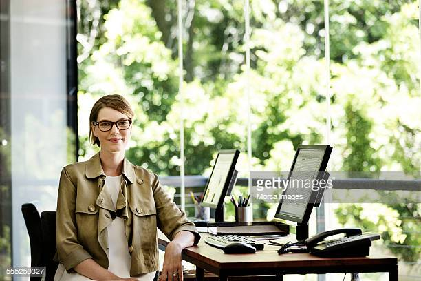 Smiling businesswoman sitting at desk in office