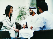 Smiling Businesswoman Sitting Face to Face With a Businessman in Traditional Middle Eastern Dress