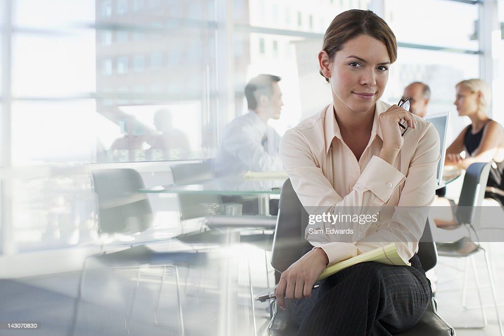 Smiling businesswoman sitting in office : Stock Photo
