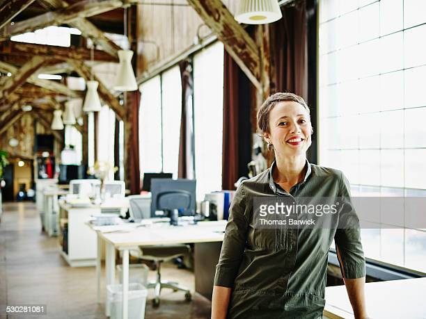 Smiling businesswoman standing at desk in office