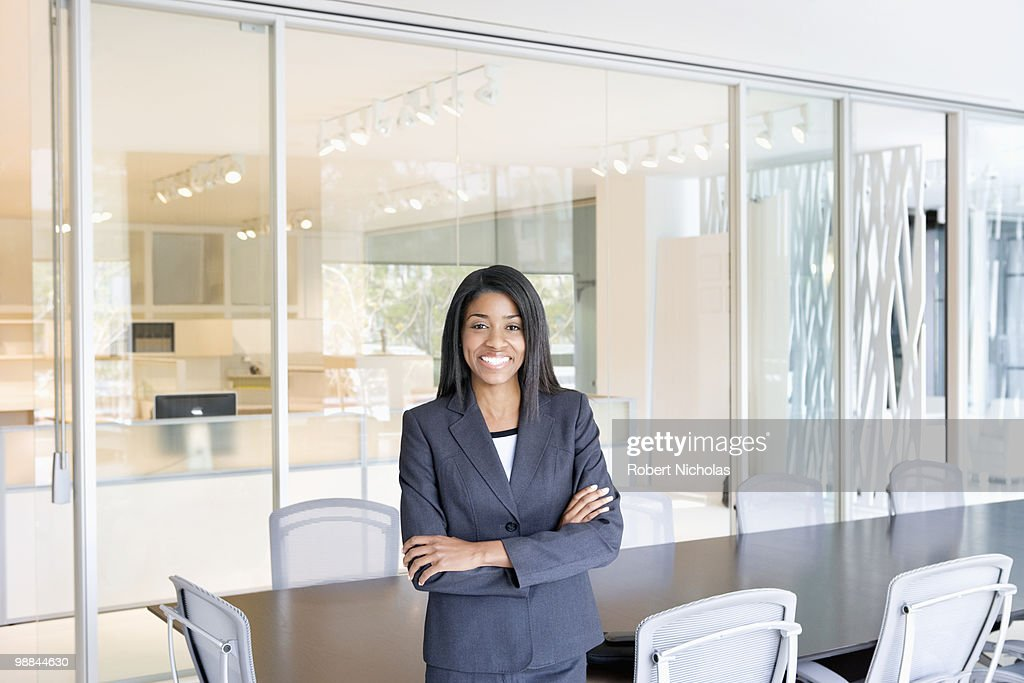 Smiling businesswoman standing in office conference room : Stock Photo