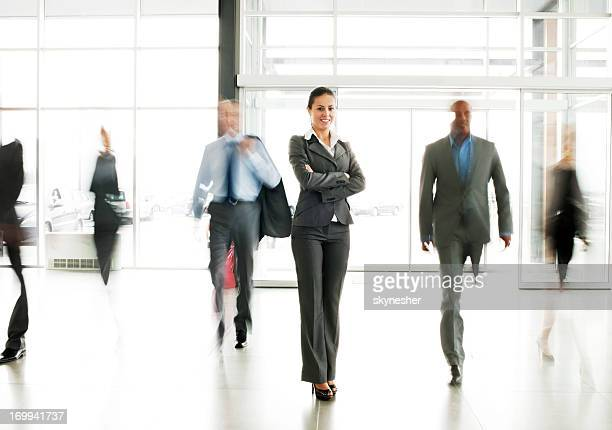 Smiling businesswoman  standing in the lobby with arms crossed.