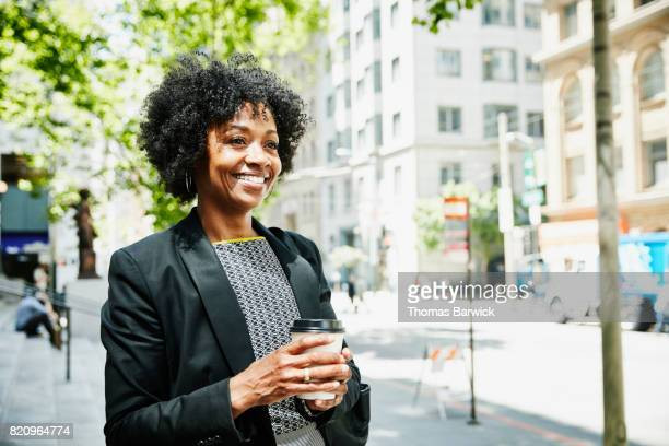 Smiling businesswoman standing on city sidewalk with cup of coffee