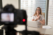 Smiling businesswoman talking on camera, happy entrepreneur vlogger recording business vlog at office desk for videoblog, filming promo ad, making presentation to website, video marketing production