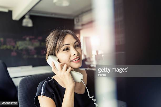 Smiling businesswoman talking on phone in office