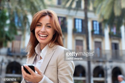 Smiling businesswoman text messaging on cell phone : Stock Photo