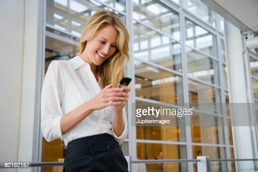 Smiling businesswoman texting : Stock Photo