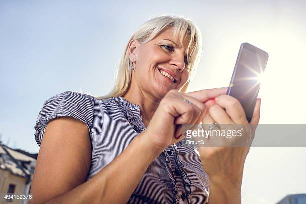 Smiling businesswoman using cell phone against the sky.