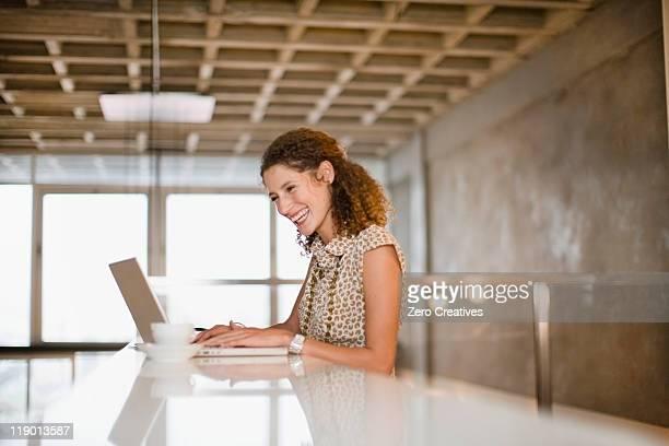 Sonriente mujer de negocios con computadora portátil