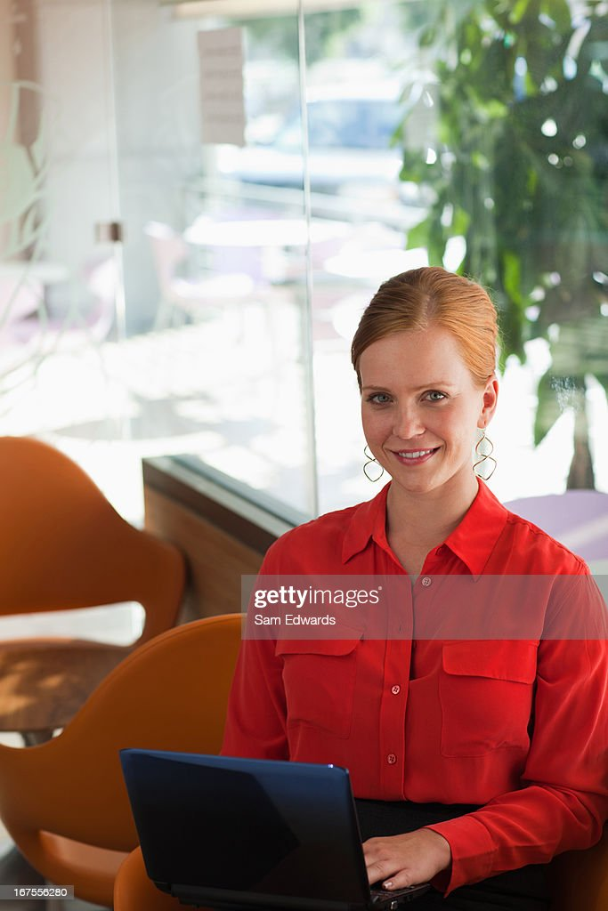 Smiling businesswoman using laptop : Stock Photo