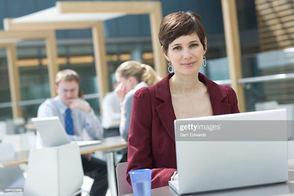 Smiling businesswoman using laptop : Stock Photo