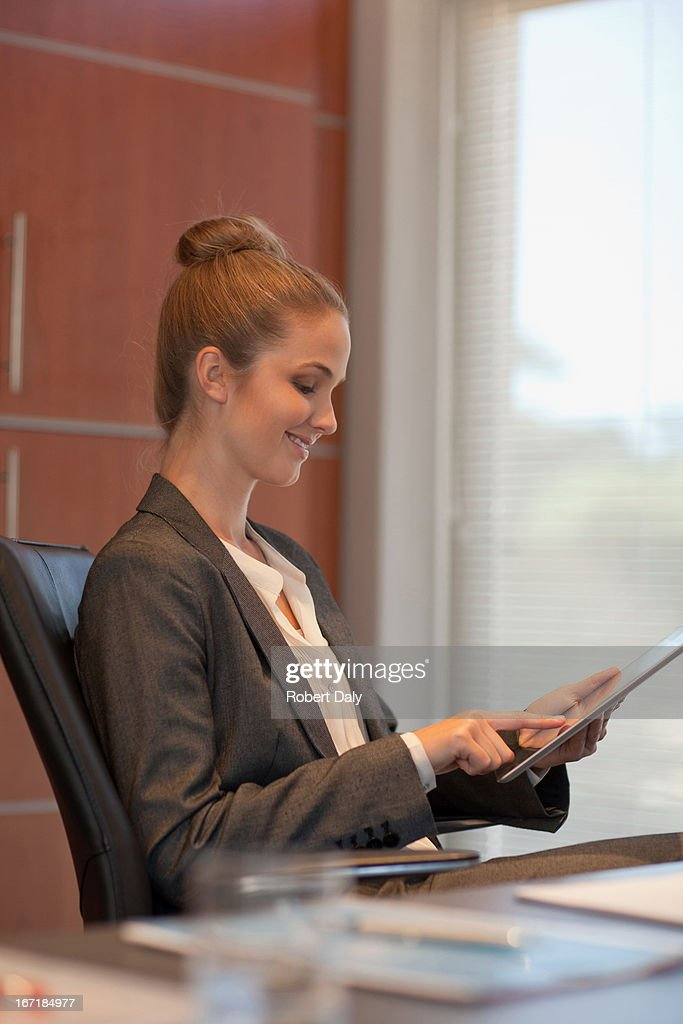 Smiling businesswoman using tablet at desk in office : Stock Photo