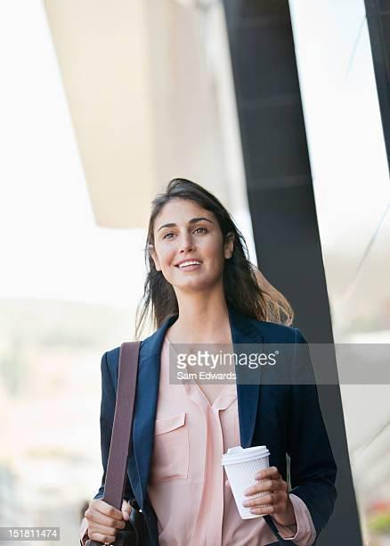 Souriant Femme d'affaires marchant avec une tasse de café