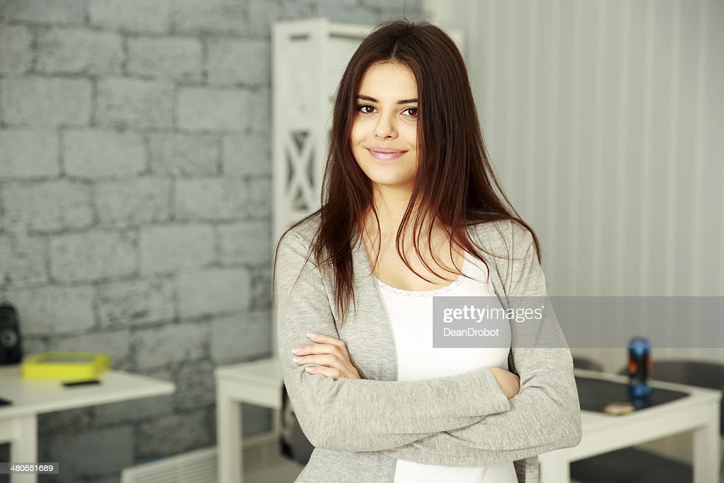 smiling businesswoman with arms folded standing : Stock Photo