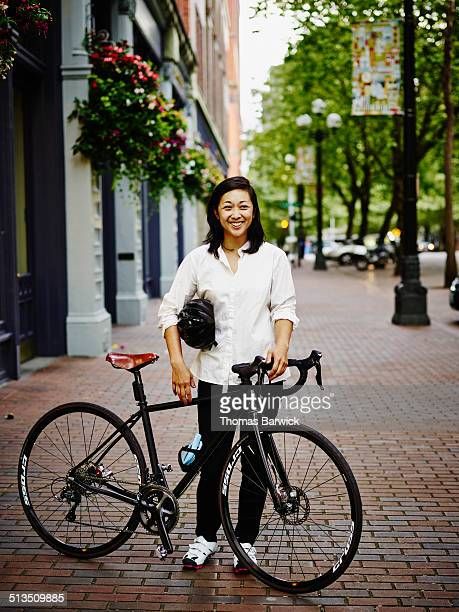 Smiling businesswoman with bike on sidewalk